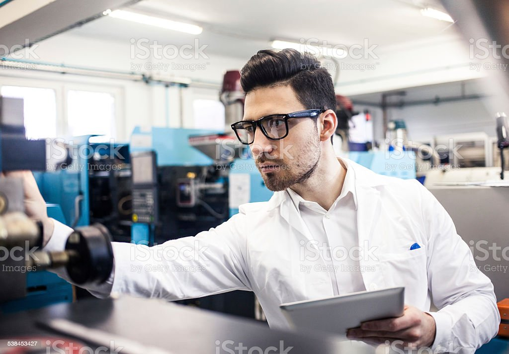 Young engineer holding digital tablet in the factory stock photo