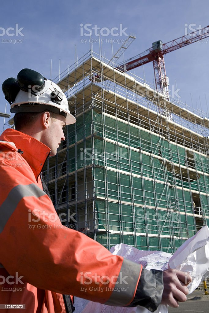 Young engineer on construction site in background scaffolding and crane royalty-free stock photo
