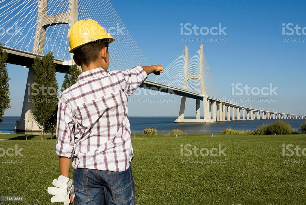 Young \'engineer\' pointing to a bridge