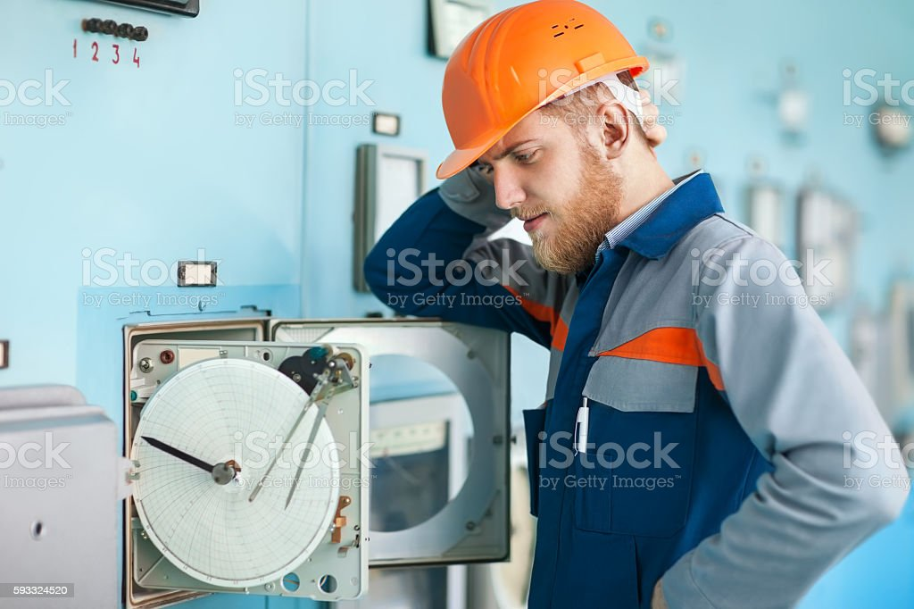 young engineer repairing equipment at control room stock photo