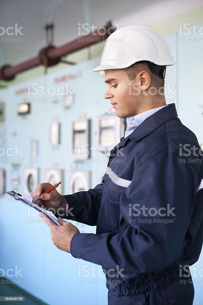 young engineer taking notes in control room royalty-free stock photo