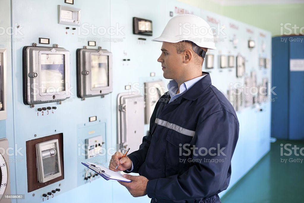 A young engineer taking notes in the control room stock photo