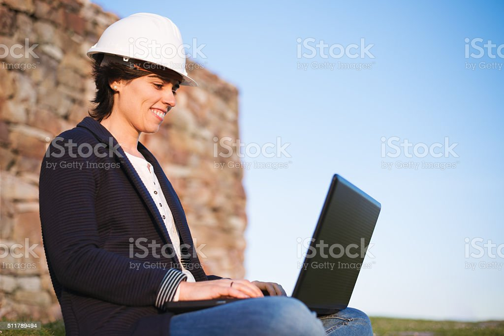 Young engineer woman entrepreneur working outdoor with laptop stock photo