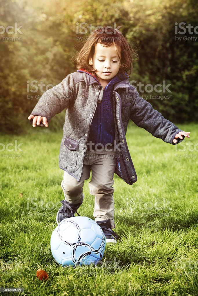 Young English boy discovering football stock photo