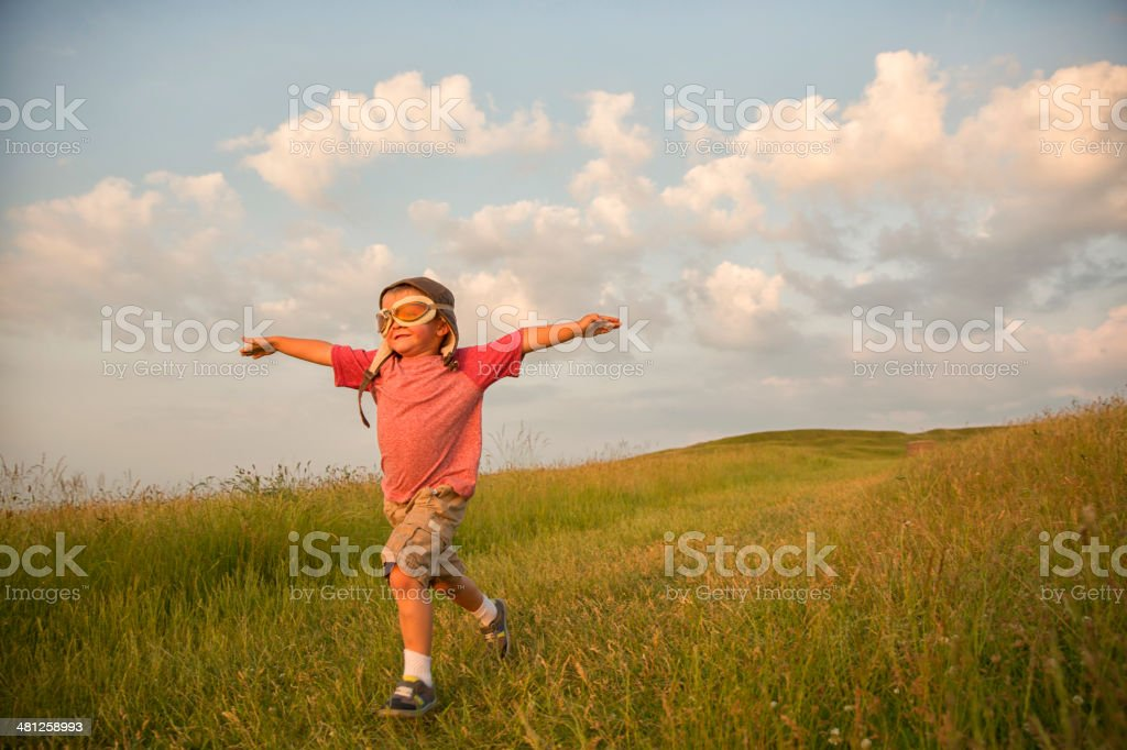 Young English Boy Imagines Flying on Hill stock photo