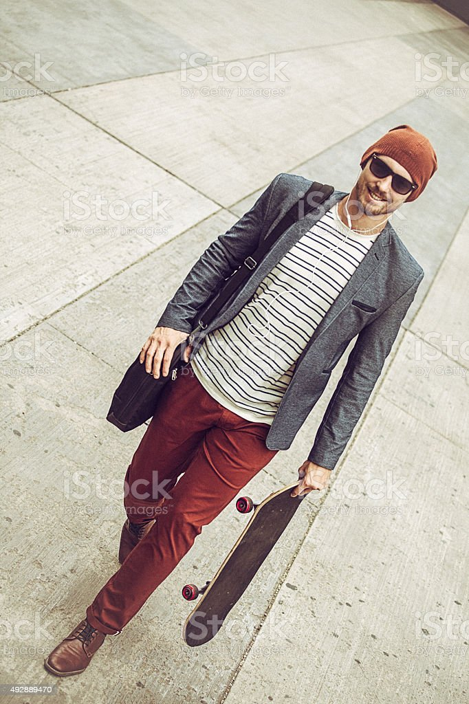 Young entrepreneur carrying skateboard on the way to work stock photo