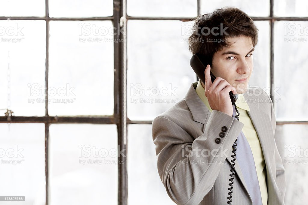 Young entrepreneur on the phone, glancing at viewer stock photo
