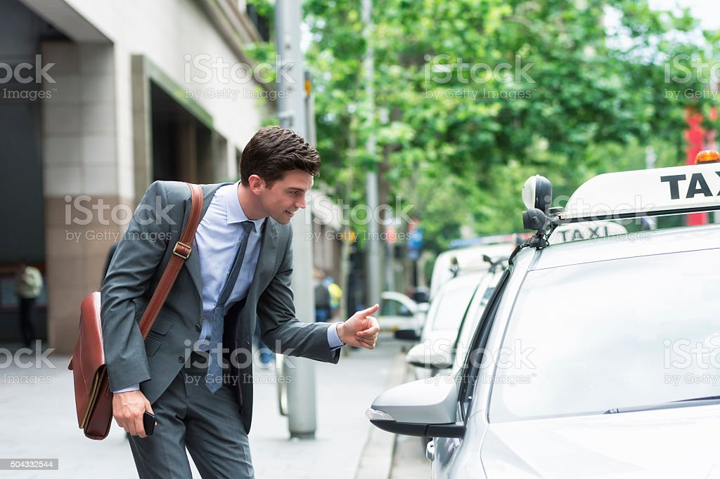 Young entrepreneur thanking taxi driver stock photo