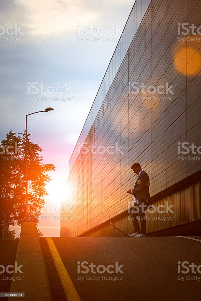 Young entrepreneur using smartphone in the urban environment at sunset stock photo