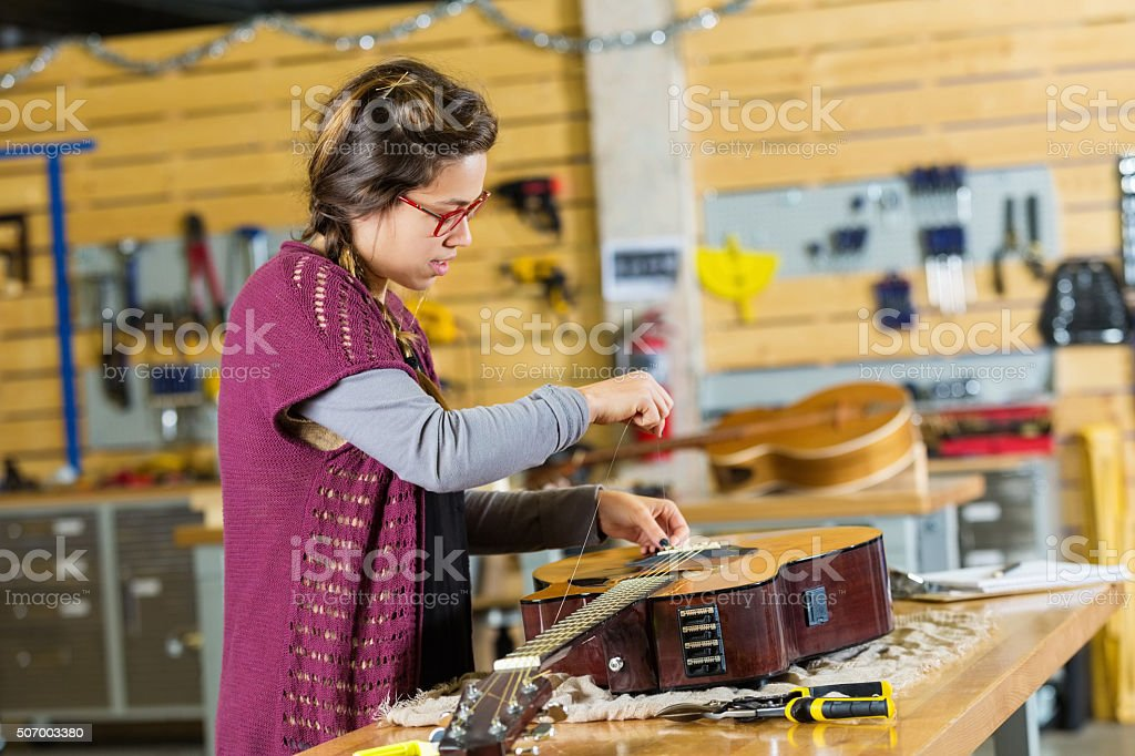Young entrepreneur working in small musical instrument repair shop stock photo