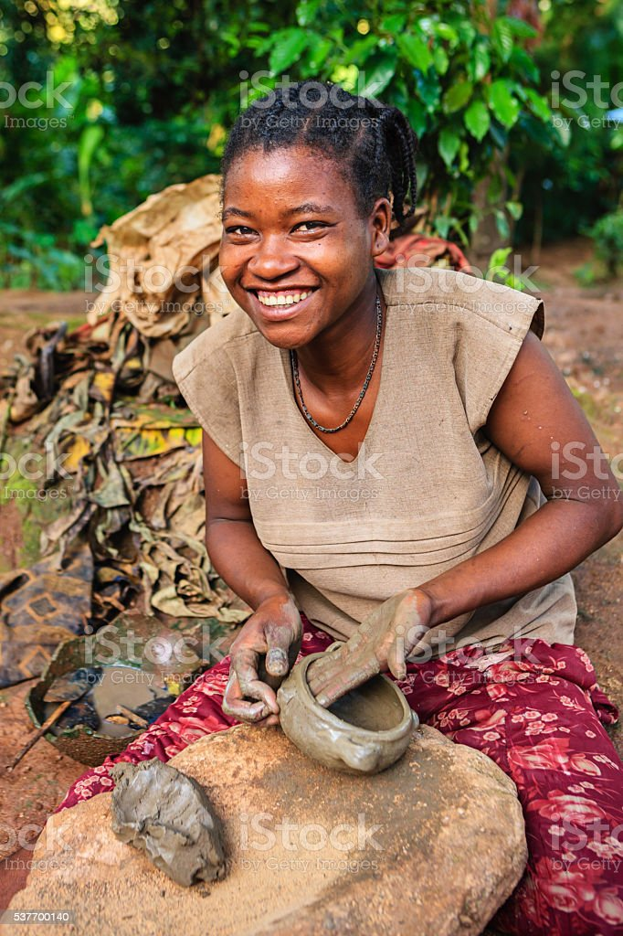 Young Ethiopian woman making pottery in Omo Valley stock photo
