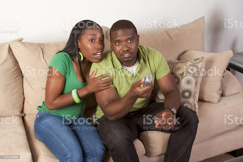 young ethnic black couple with remote control stock photo