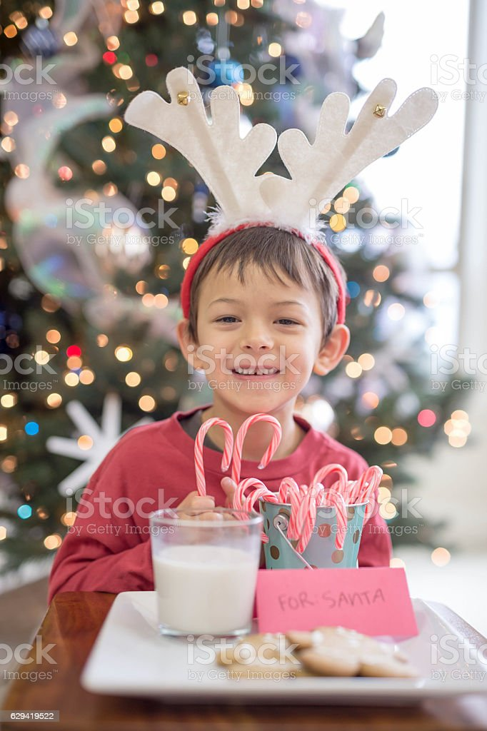 Young ethnic boy ready for Santa to come stock photo