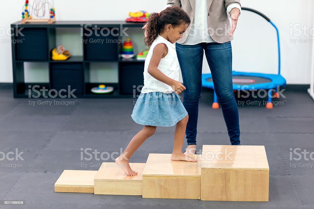 Young ethnic child walking up steps in therapy stock photo