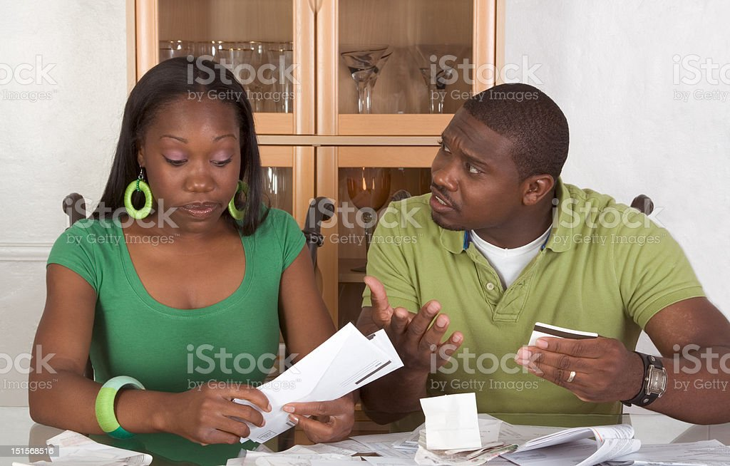 Young ethnic couple by table overwhelmed with bills stock photo