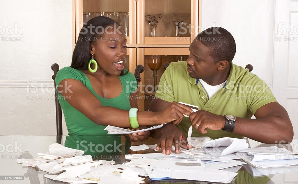 Young ethnic couple near table overwhelmed by bills stock photo