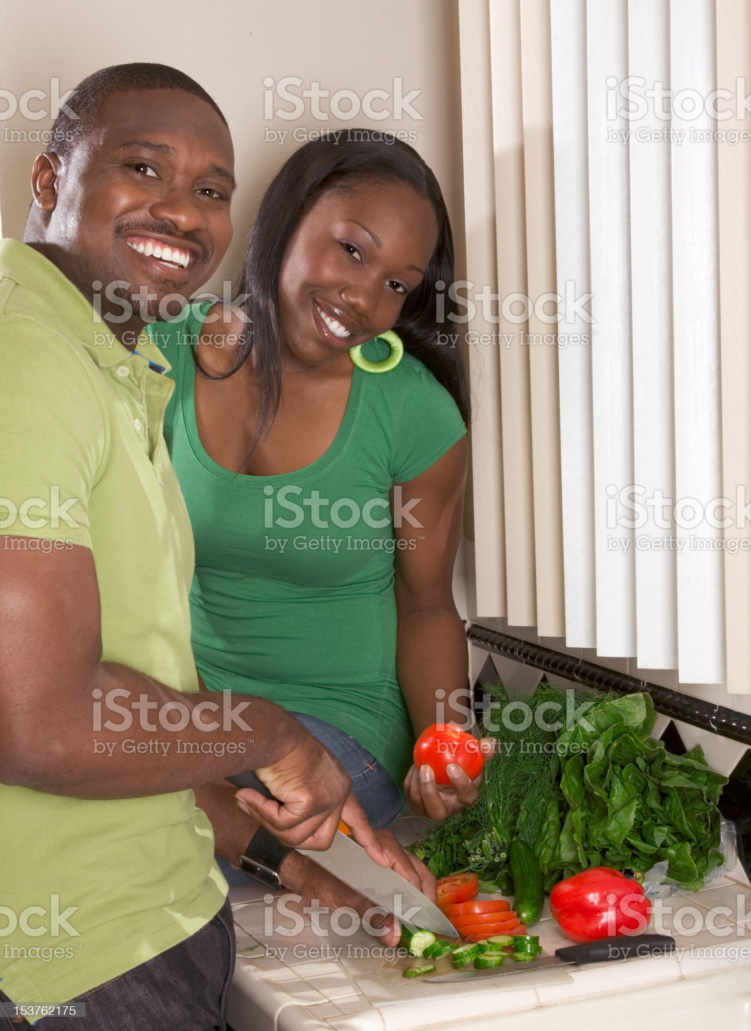 Young ethnic couple on kitchen slicing vegetables royalty-free stock photo
