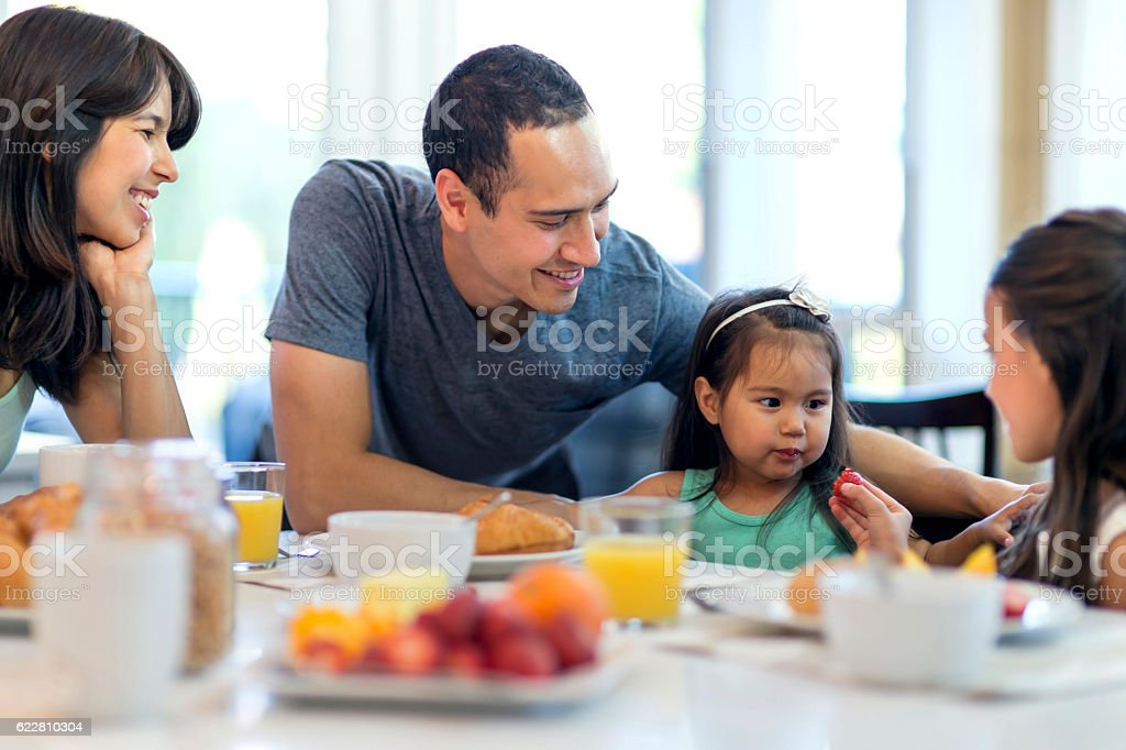 Young ethnic family eating a healthy breakfast together stock photo