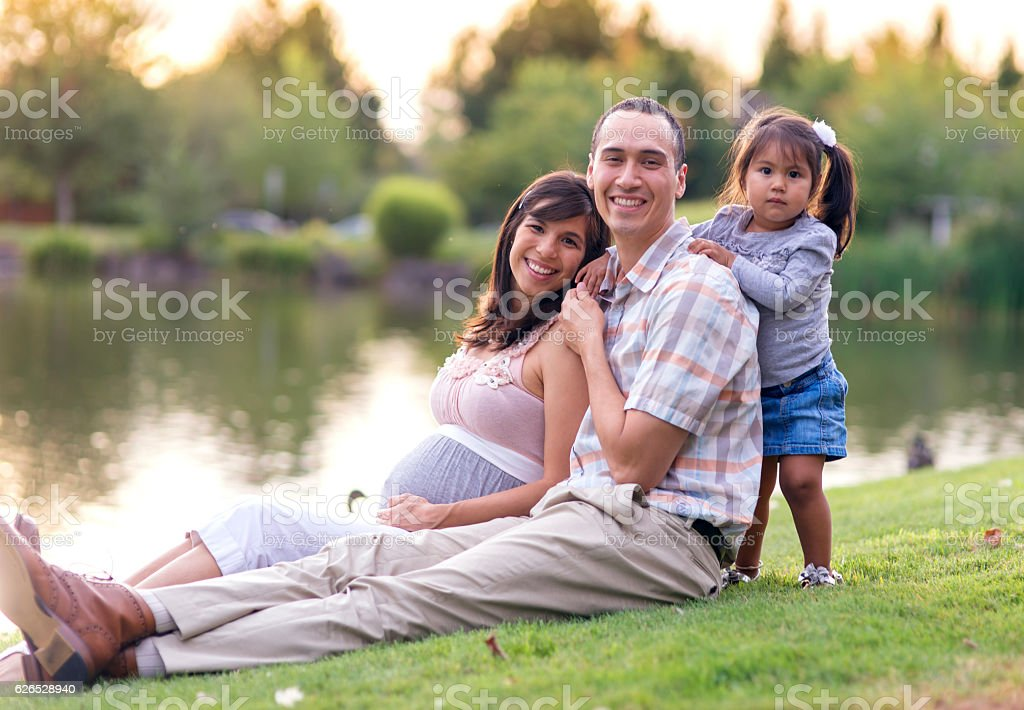 Young ethnic family sitting together in the park stock photo