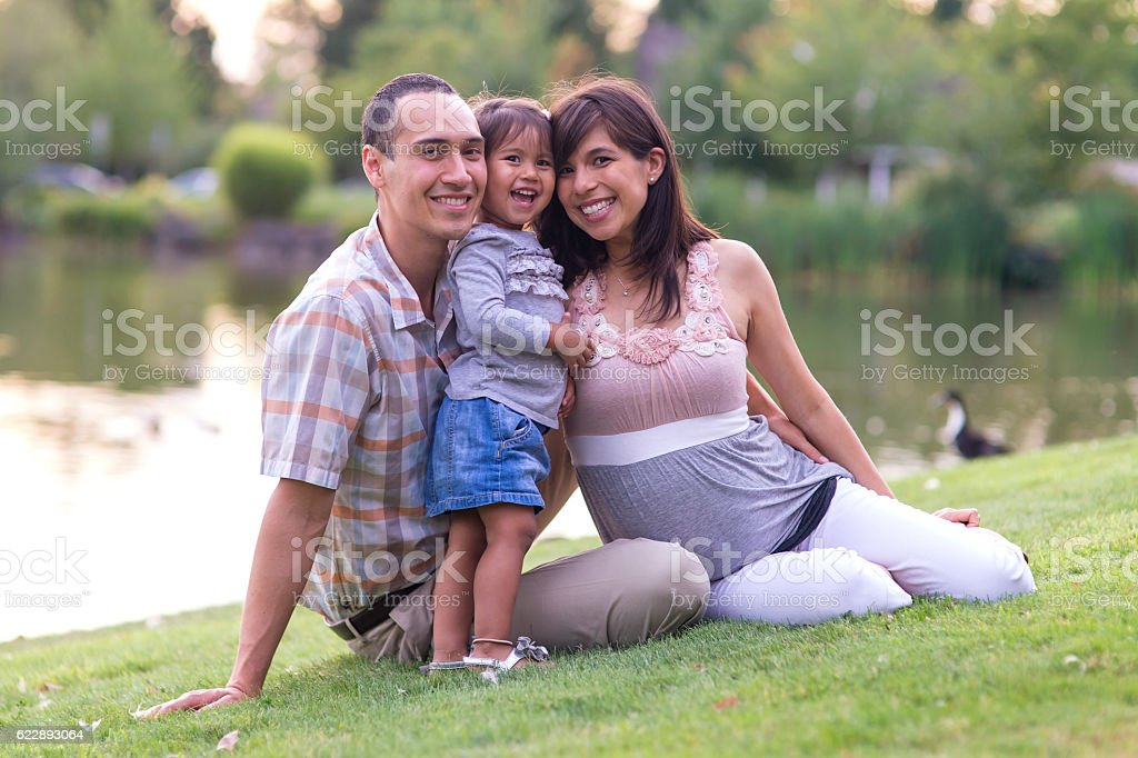 Young ethnic family smiling while sitting in the local park stock photo