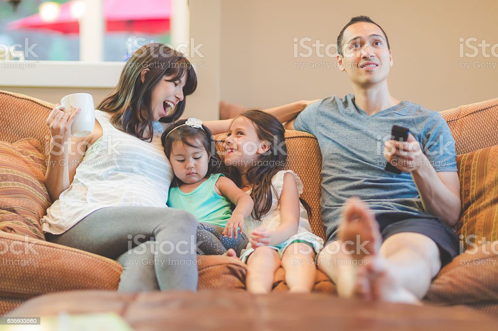 Young ethnic family watching television together and relaxing stock photo