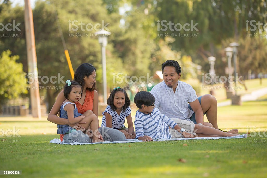 Young ethnic family with three children relaxing together stock photo