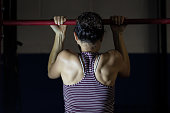 Young ethnic female working out in a gym doing pull