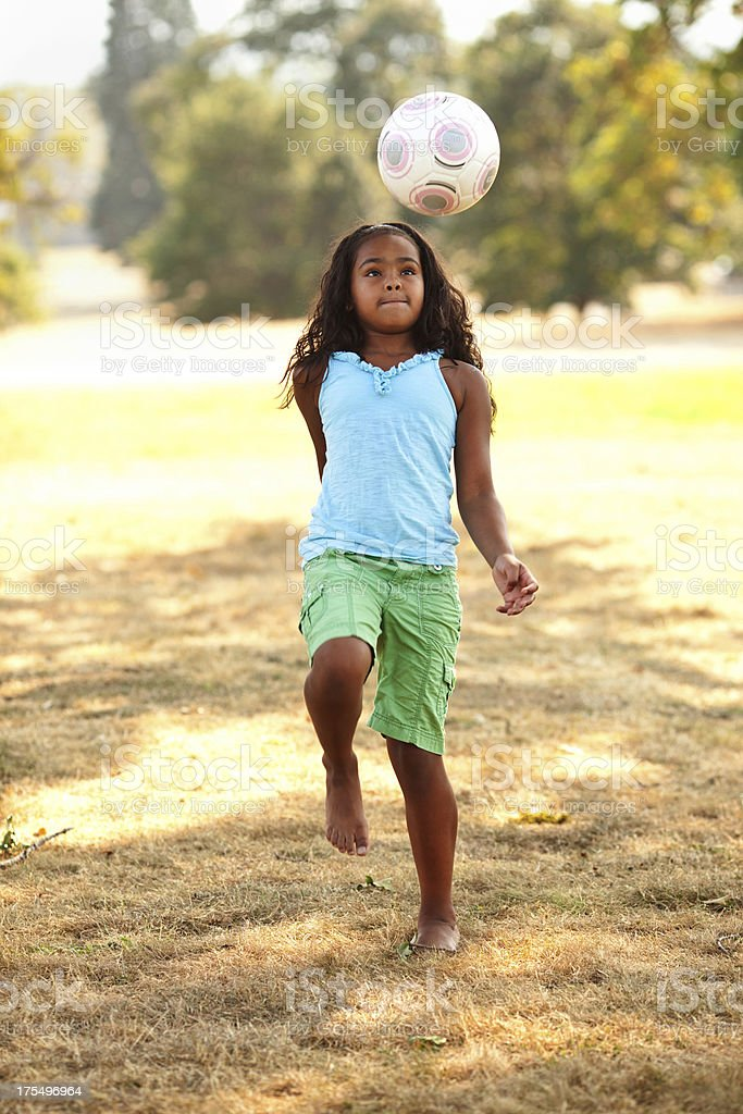 Young ethnic girl playing soccer in the park. royalty-free stock photo