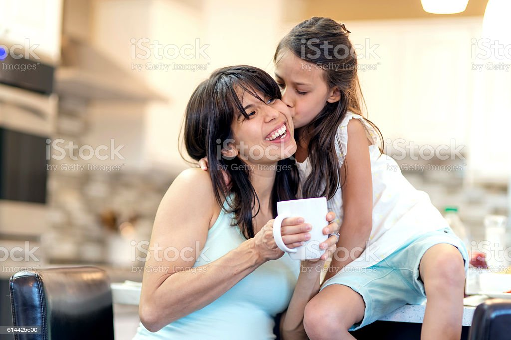 Young ethnic mother getting a kiss from her young daughter stock photo