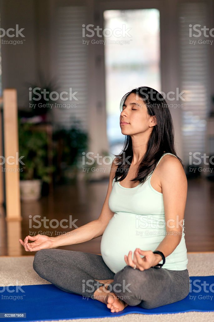 Young ethnic pregnant woman meditating on a yoga mat stock photo