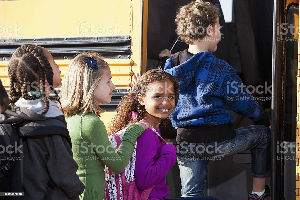 Young ethnically diverse students boarding bus stock photo