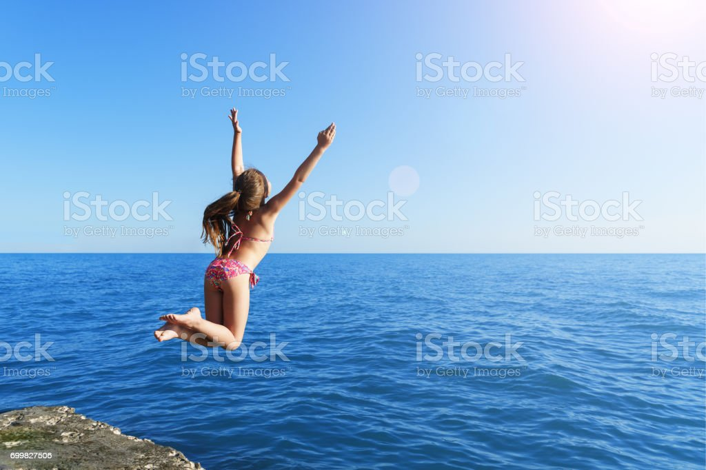 young european cute girl is jumping and flying to the calm blue sea from concrete breakwater towards summer soft sun stock photo
