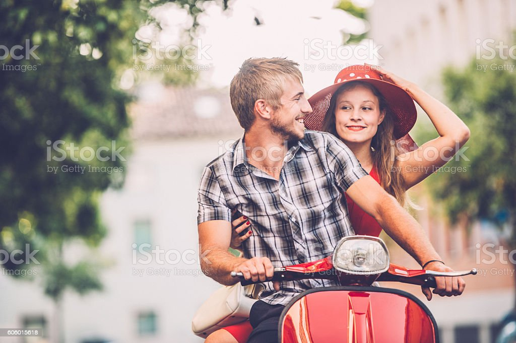 Young Excited Couple Portrait on a Vintage Scooter stock photo