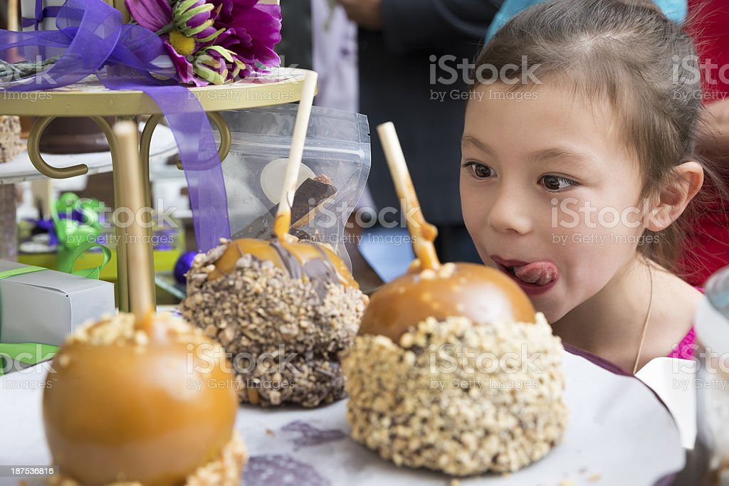 Young excited girl in candy store looking at caramel apples stock photo
