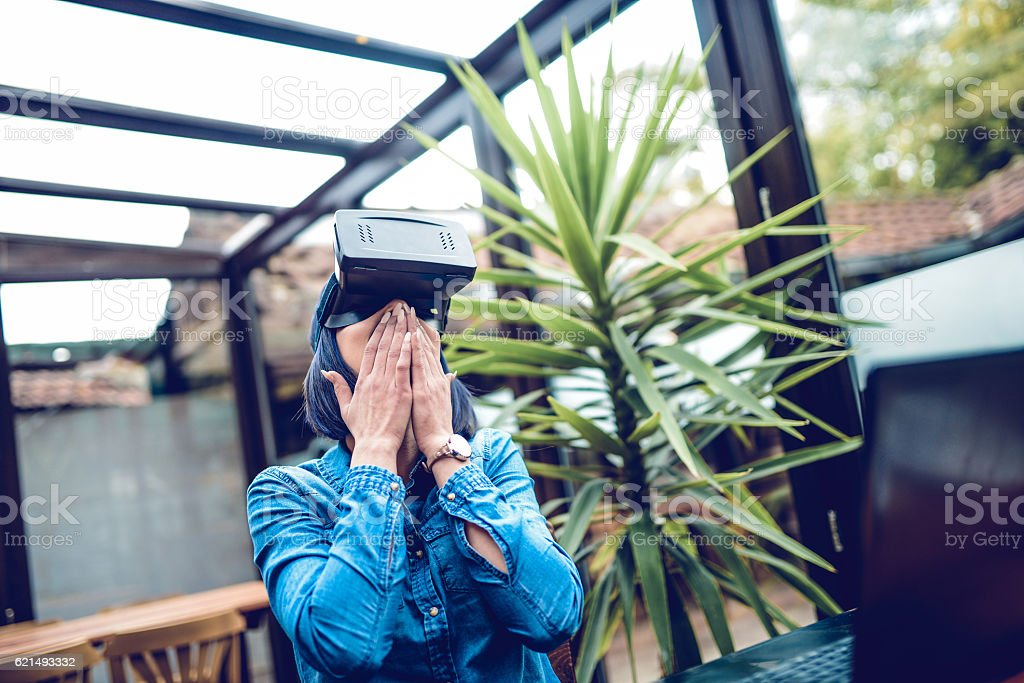 Young Excited Woman Having Fun with Virtual Reality Simulator stock photo