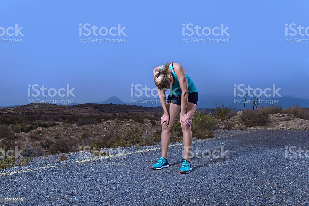 young exhausted sport woman running outdoors on asphalt road breathing stock photo