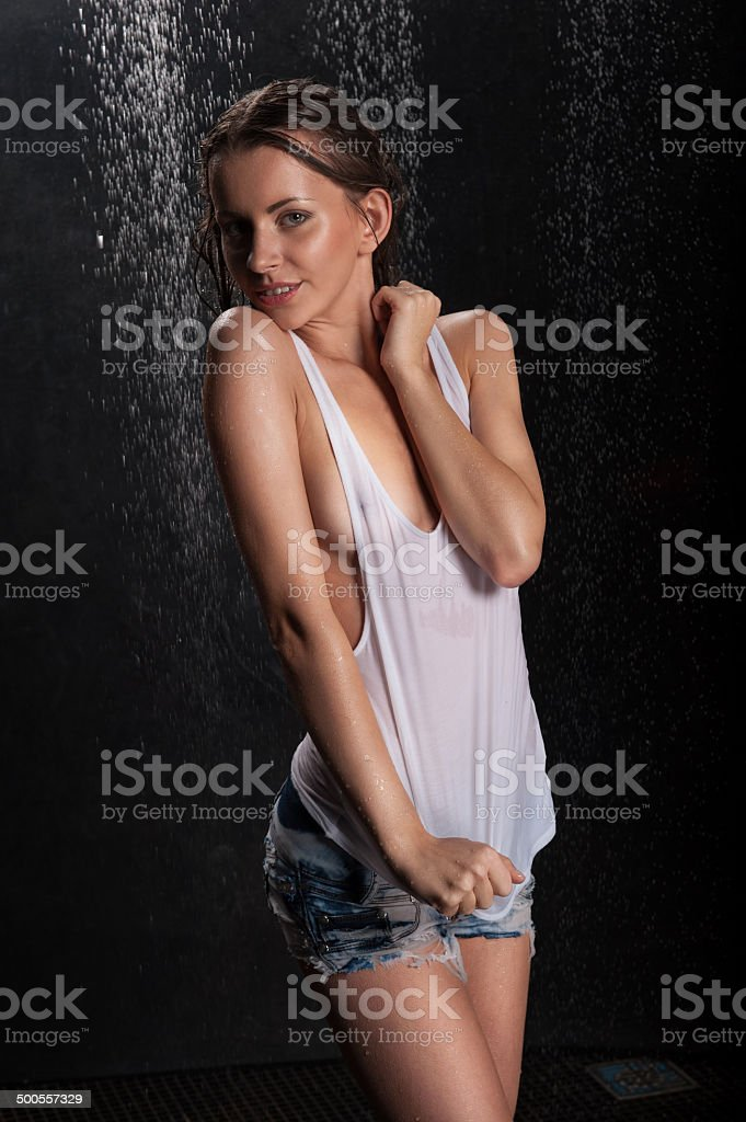 Young expressive sexy woman with T-shirt in water splashes and stock photo