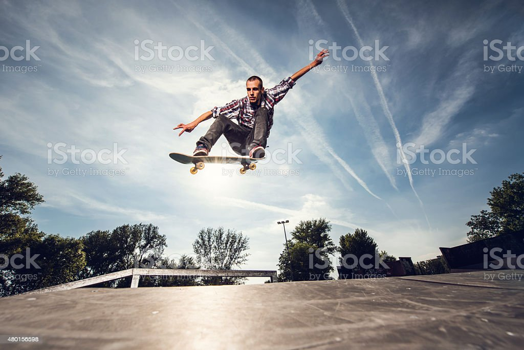 Young extreme skateboarder practicing at the park. stock photo