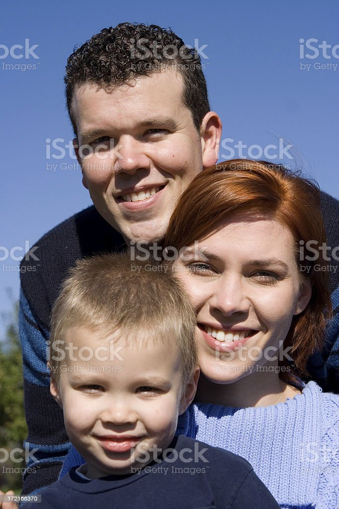 Young family against blue ksy royalty-free stock photo