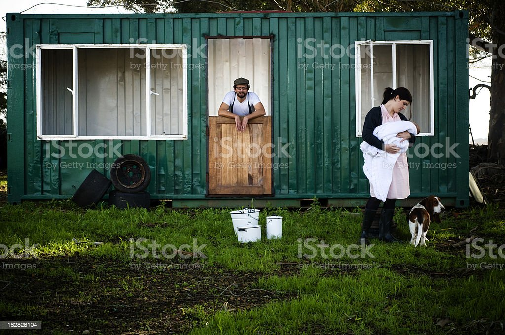 Young family and dog with unfinished, green container home royalty-free stock photo