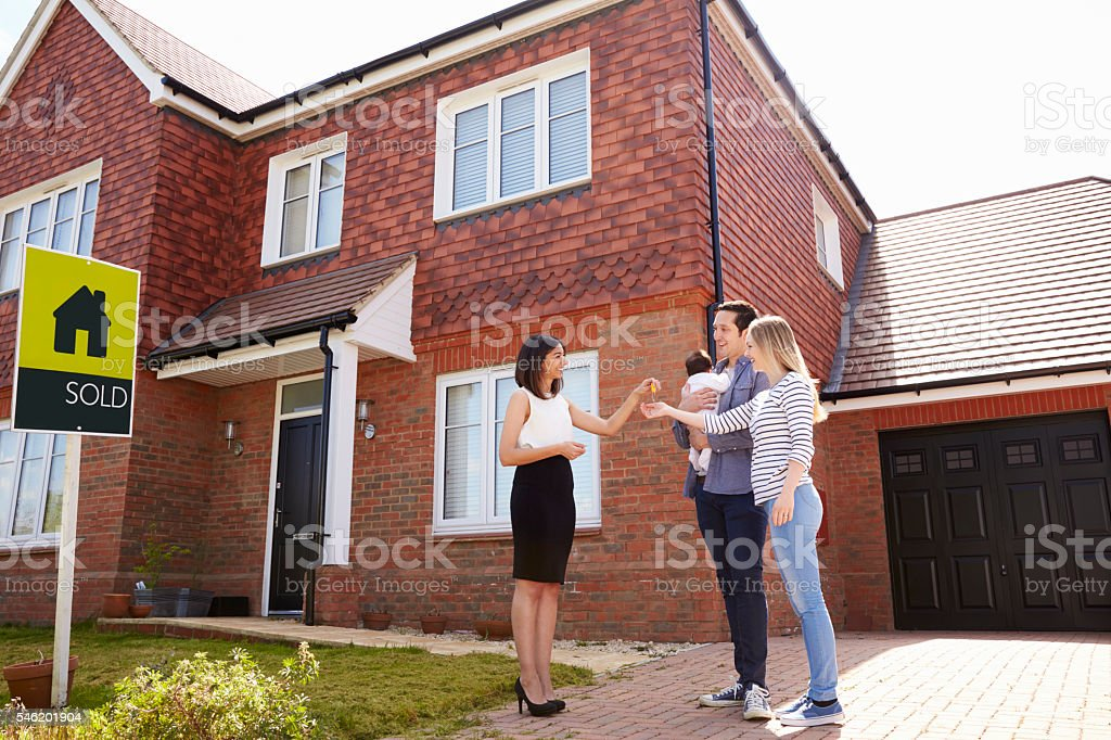 Young Family Collecting Keys To New Home From Realtor stock photo