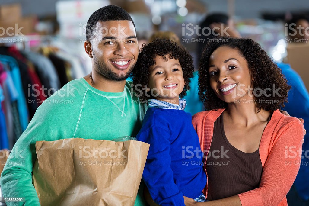 Young family donates items to food drive stock photo
