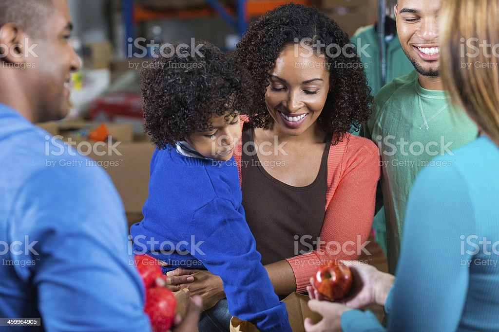 Young family donating or receiving donations at food bank stock photo