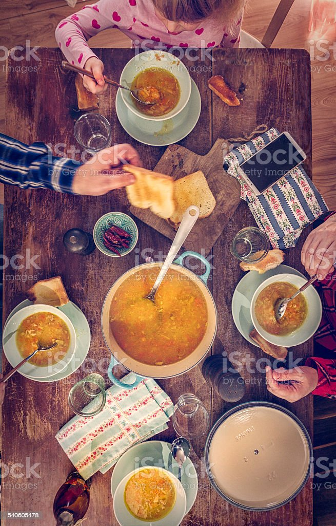 Young Family Eating Chicken Soup with Carrots and Parsnips stock photo