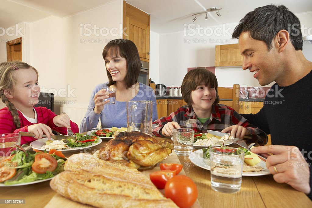 Young family eating together at kitchen table royalty-free stock photo