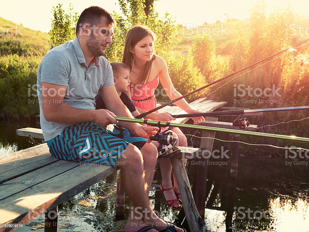 Young family fishing holiday with wooden planked footway stock photo