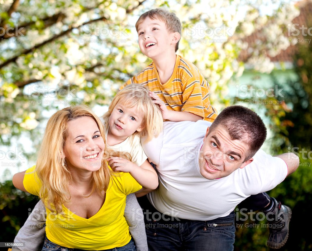 Young family giving their two children piggyback rides royalty-free stock photo