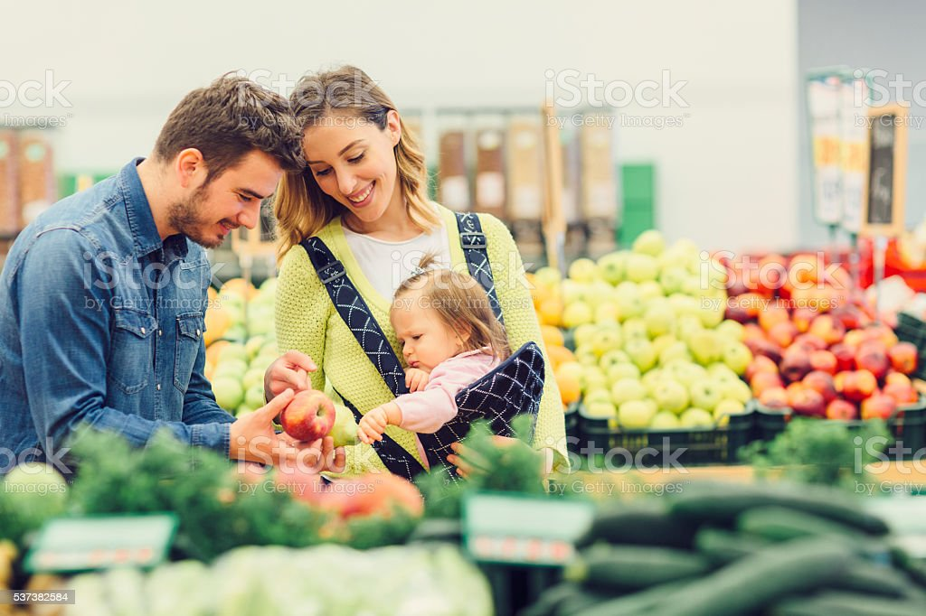 Young Family Groceries Shopping In Local Supermarket. stock photo