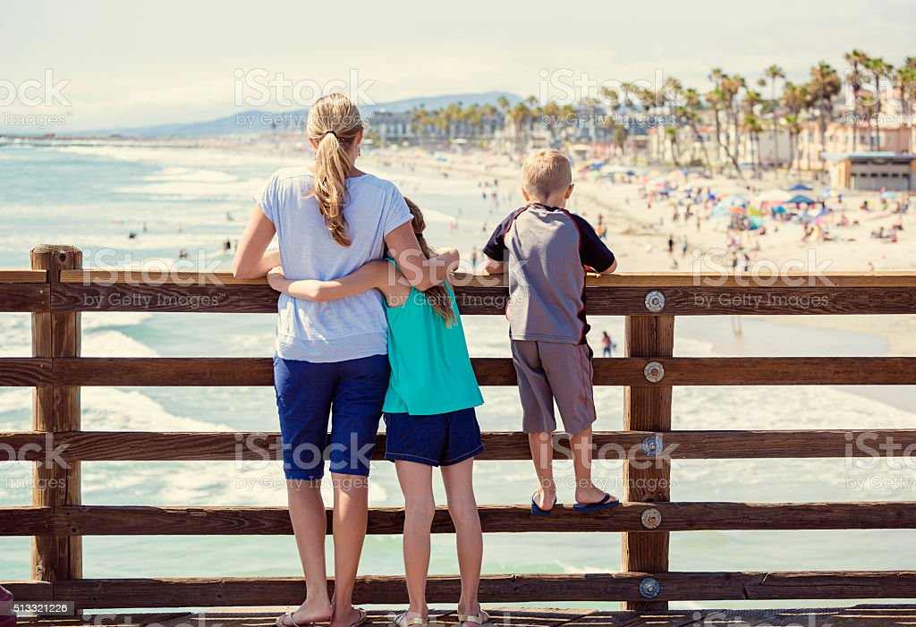 Young family hanging out on an ocean pier on vacation stock photo