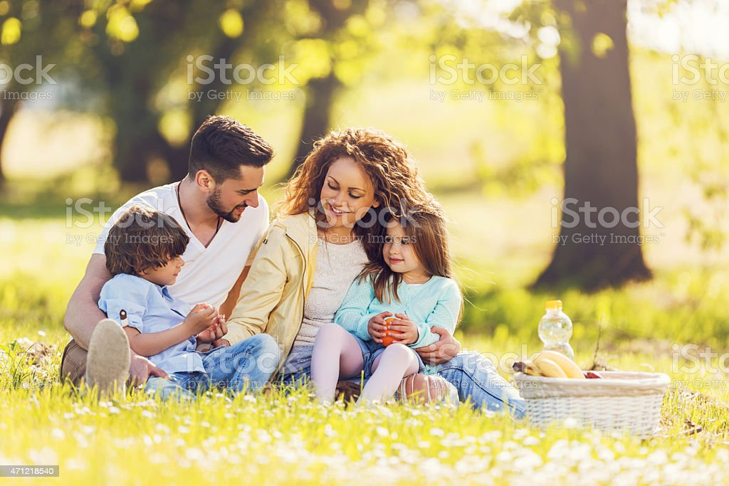 Young family having a picnic outdoors and communicating. stock photo